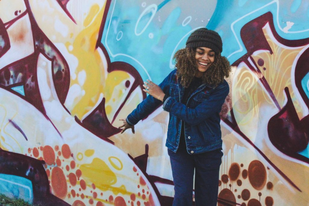 woman-standing-against-wall-with-grafiti-behind
