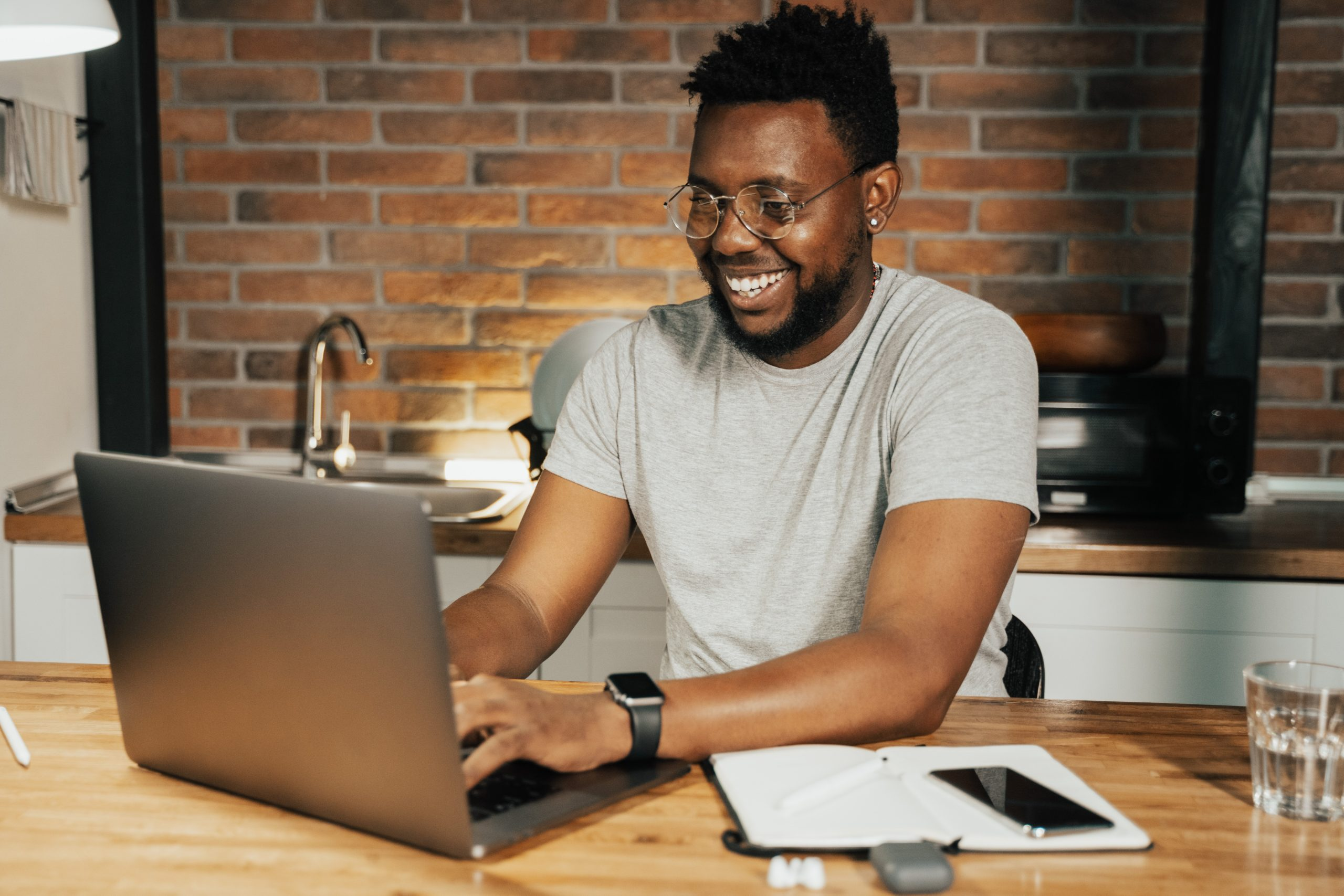 Smiling man on laptop building a personal brand