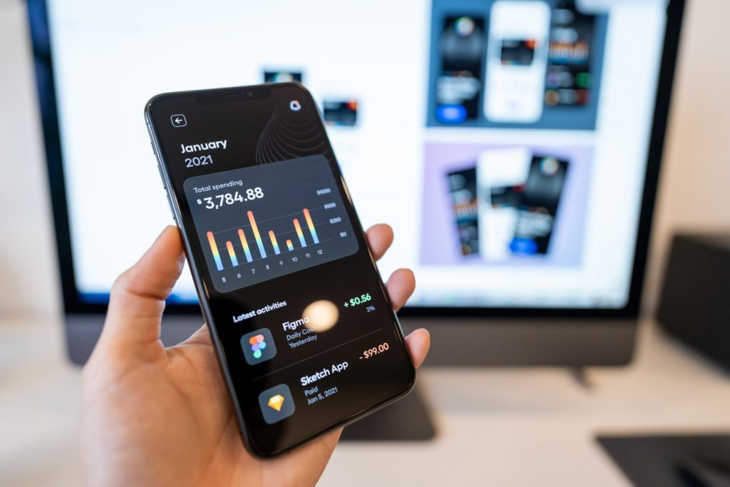 Man holding smartphone with app open against a desktop