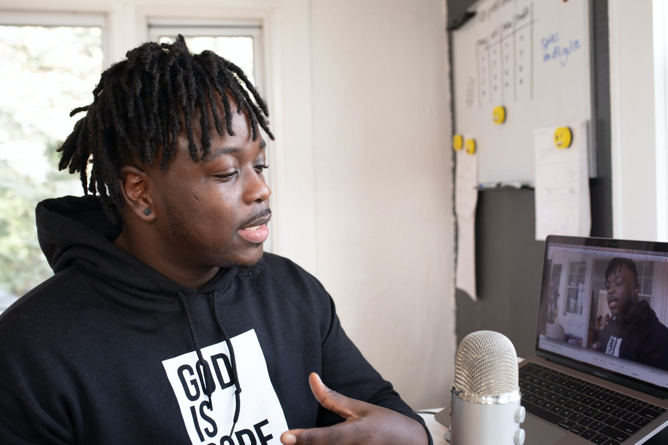 Man wearing black top speaking into a micrphone recording a podcast for his marketing strategy