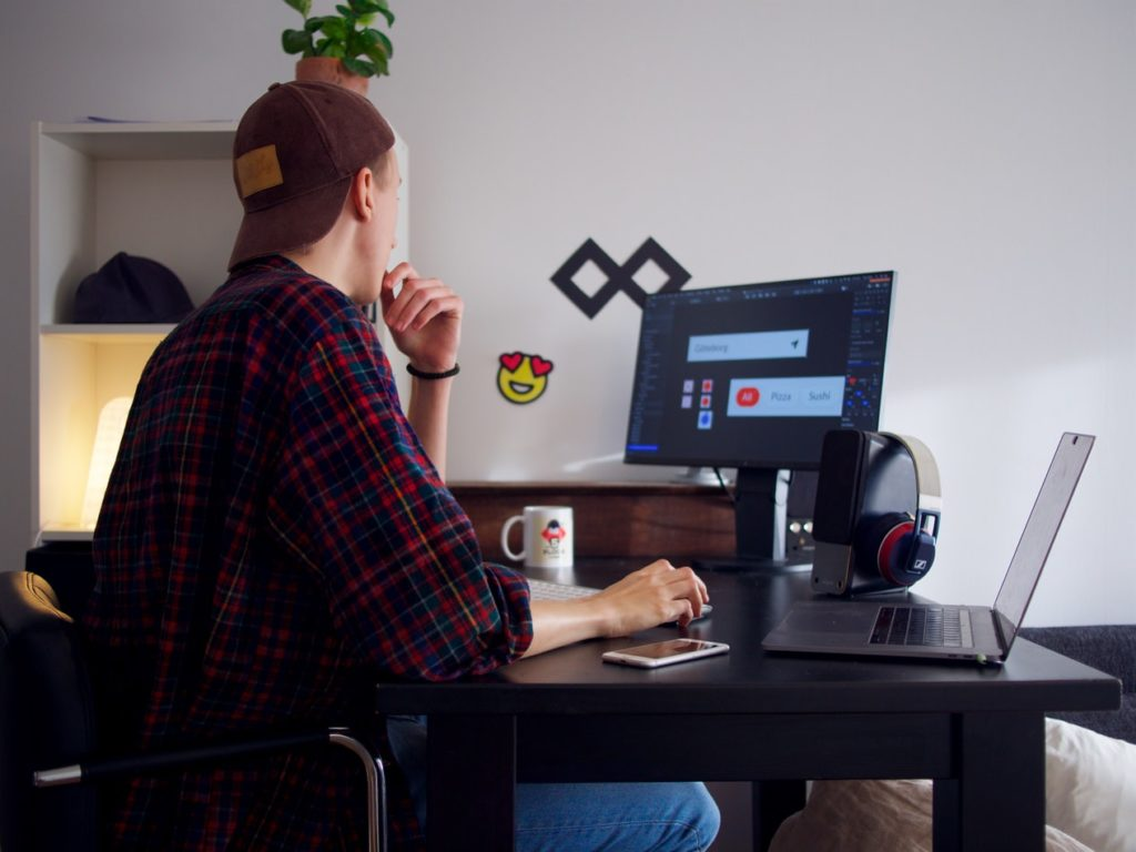A man sitting at his desk working on his laptop as a freelancer