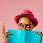 A person wearing a pink hat holding a blue marketing strategy book