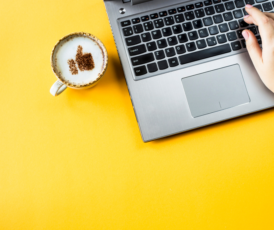 A person with a cup of coffee on a laptop looking how to improve search ranking