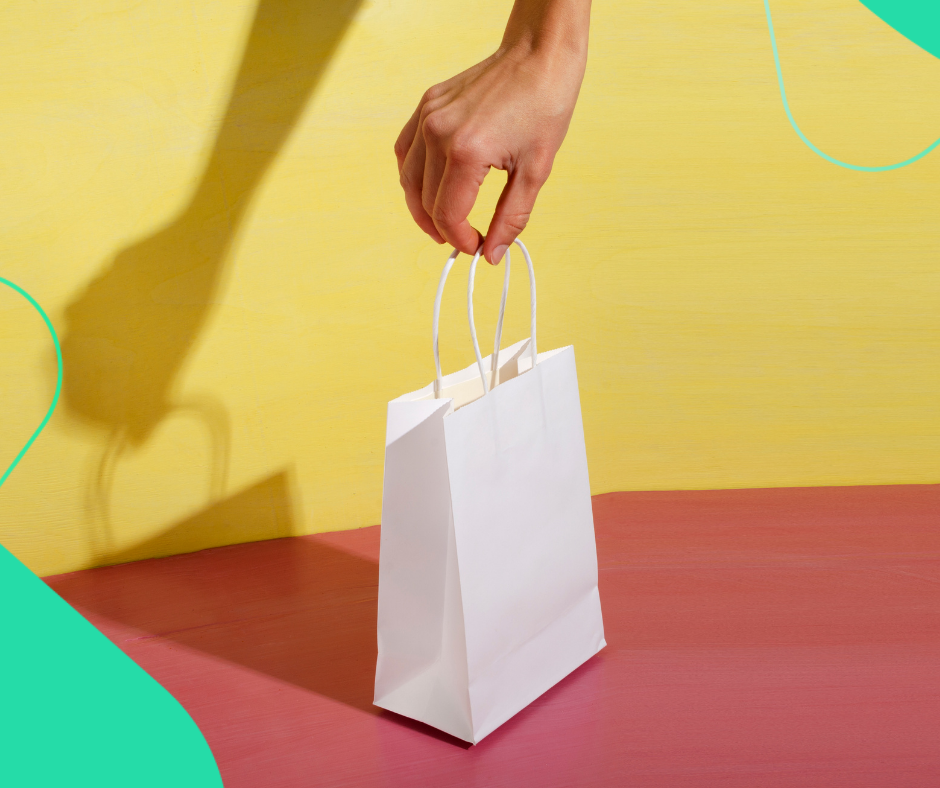 A person holding a white shopping bag against a red and yellow background